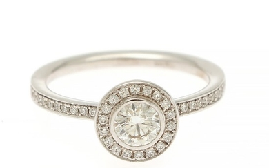 A diamond ring set with a brilliant-cut diamond encircled by numerous brilliant-cut diamonds, mounted in 18k white gold. Size 54.