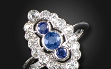 A sapphire and diamond cluster ring, set with three graduated circular-cut sapphires within a surround of graduated circular-cut diamonds in white gold, size O ½