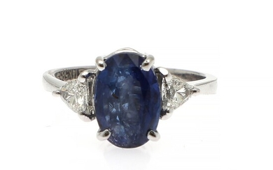 A sapphire and diamond ring set with an oval-cut sapphire flanked by two trilliant-cut diamonds, mounted in 14k white gold. Size 52.5.
