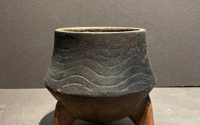 A unusual Chinese earthen tripod vessel. Wavelines incised on...