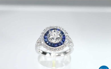White gold ring with a large diamond surrounded by sapphires and brilliant cut diamonds.