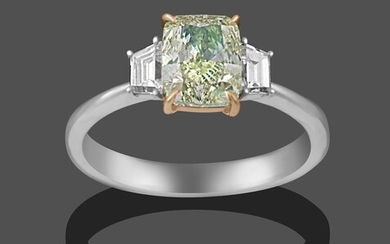 A Diamond Three Stone Ring, the central fancy light greenish-yellow...