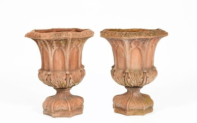 A pair of terracotta garden urns in the manner of Royal Doulton, octagonal section, each cast with arch panels to the body, the foot cast with flowerhead motif, unsigned, 50cm. high, (2) Provenance The collection of Pam and Mark Taylor.