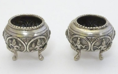 A pair of white metal salts with deity decoration.