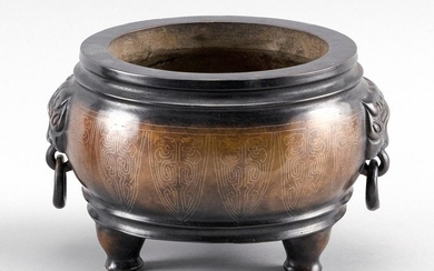 CHINESE BRONZE CENSER In squat form, with mask handles, silver inlaid lappet design about the body, and tripod base.