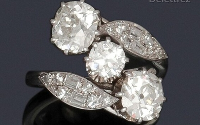 """Ring """" Toi and Moi """" in white gold, made up of two cushion-shaped diamonds set in a foliage setting of baguette-cut and brilliant-cut diamonds, in an entourage of foliage. Diamond weight principaux : about 1.60 carat each, the central one about 0.80..."""