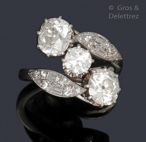 "Ring "" Toi and Moi "" in white gold, made up of two cushion-shaped diamonds set in a foliage setting of baguette-cut and brilliant-cut diamonds, in an entourage of foliage. Diamond weight principaux : about 1.60 carat each, the central one about 0.80..."