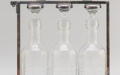 """SILVER PLATED TANTALUS WITH THREE CRYSTAL DECANTERS Tantalus with maker's mark """"MMCo"""". Decanters etched with wheat, thistles and jun.."""