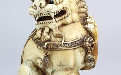 Temple lion made of mammoth ivory, China c. 1920, one piece carved figure of a sitting temple lion with 3 loosely hanging bells, lucky knot on the back, h 18 cm, weight 1457 g, badly restored area on the left front leg (probably small crack), with...