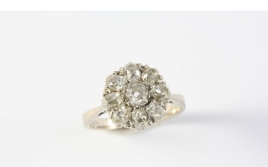 A DIAMOND CLUSTER RING the old cushion-shaped diamond is set...