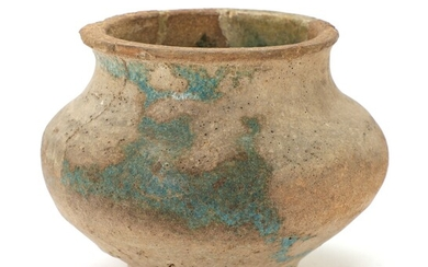 A Kashan (partly) blue-glazed moulded pottery jar, Persia, 13th century. H. 11.5 cm.