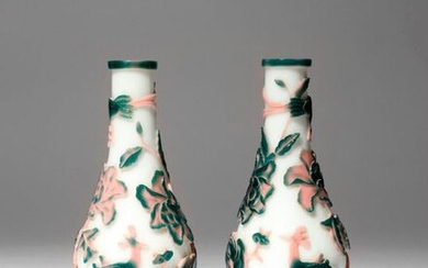 A PAIR OF CHINESE BEIJING PINK AND GREEN-OVERLAY GLASS 'PHOENIX' BOTTLE VASES 19TH CENTURY Each carved through pale pink and dark green glass to a white ground with a standing phoenix gazing up at its partner in flight above, with large peony blooms...