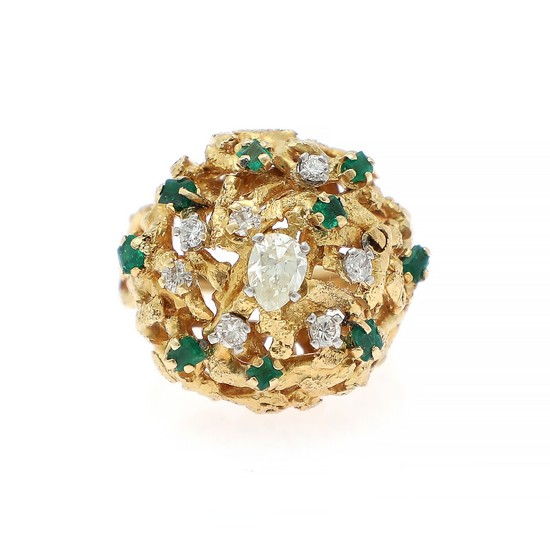 A diamond and emerald ring set with a pear-shaped diamond encircled by numerous brilliant-cut diamonds and baguette-cut emeralds, mounted in 18k gold. Size 53.