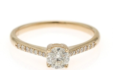 A diamond ring set with a brilliant-cut diamond flanked by numerous diamonds, mounted in 14k gold. Size 54.