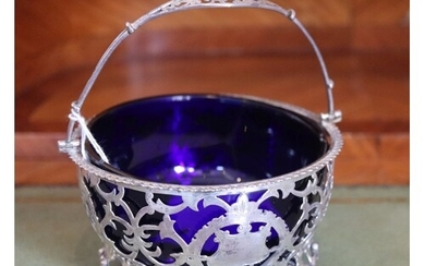 A late Victorian pierced silver sugar basket with blue glass...