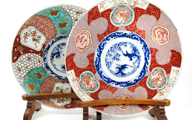 A matched pair of Imari chargers on wooden stands