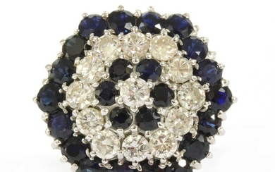A white gold diamond and sapphire target cluster ring