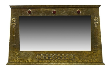 An Arts and Crafts brass framed over-mantel mirror with ceramic...