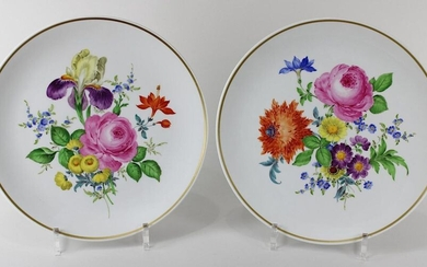 Pair of plates Meissen, 2nd half of the 20th century, decorated with gold and coloured ornaments, décor: flowers, among others red rose and forget-me-not, gold ribbon, diameter each ca. 25,7 cm, on the bottom blue sword marks, at the rim blue mark...