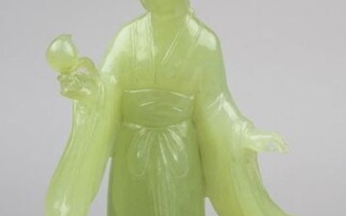 Young woman with flower, jade figure, China circa 1920, carved from a piece of light green jade, the foot bumped on the back, h 18.5 cm, weight 397.7 g, in a matching fabric covered, internally padded box, 31 x 13 cm, h 9 cm, base missing. 2483-006