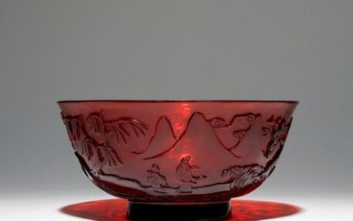 A CHINESE BEIJING RUBY GLASS BOWL QIANLONG 1736-95 The flaring U-shaped body raised on a short spread foot, the translucent red glass carved with a continuous scene of figures in a mountainous landscape, with pine, willow and dwellings dispersed...