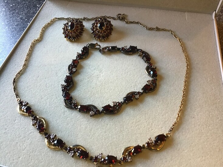 A garnet jewellwey set comprising a necklace, a bracelet and a pair of ear clips each set with numerous garnets, mounted in gold plated sterling silver.