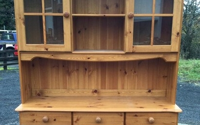 A pine dresser with moulded cornice above two glazed...
