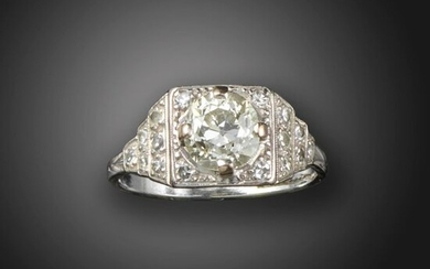 An Art Deco diamond solitaire ring, the old circular-cut diamond is set within a square surround with old circular-cut diamonds to the stepped shoulders in platinum, size M 1/2