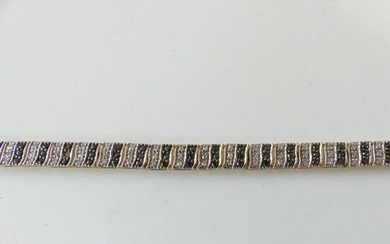 BRACELET in 750°/°° yellow gold set with black diamonds interspersed...