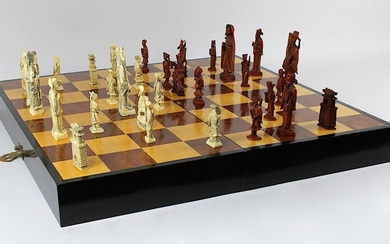 Chess set with ivory pieces, China circa 1940, one part of the pieces made of white ivory, the other part of brown dyed ivory, each piece finely carved and with blackened incised decoration, in the original box, which also serves as a board when...
