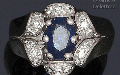 "Ring "" Fleur "" in white gold, adorned with an oval sapphire facetted in dome-shaped surrounds set with brilliant-cut diamonds forming the petals. Work from the 1950s. Tour of doigt : 53. P. Brut : 9.1 g."
