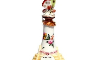 A Chelsea scent bottle c.1755, modelled as a bottle contained in a yellow wicker basket, the neck painted with sprays of flowers, moulded with a bottle ticket inscribed 'Eau de Senteur', with a gilt metal mount and a stopper formed as a colourful...