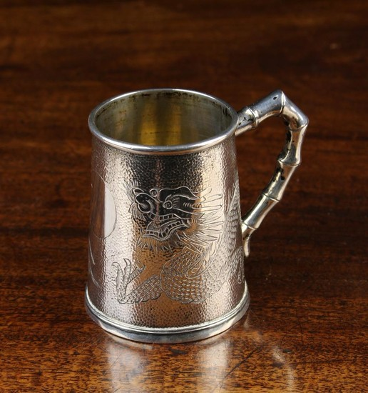 A Chinese Export Sterling Silver Christening Mug engraved with dragons around a vacant roundel on a