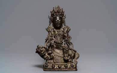 A Chinese bronze figure of Guanyin on a...