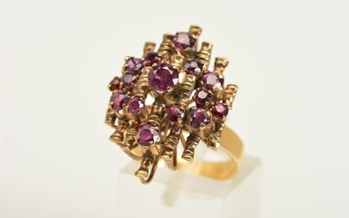 A GARNET DRESS RING, a tiered ring with open metal work set ...