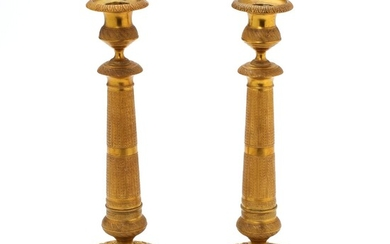 A pair of French 19th-20th century Empire style gilt bronze candlesticks. H. 28.5 cm. (2)...