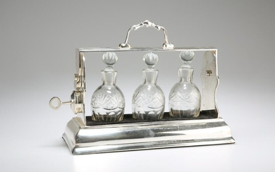 AN EDWARDIAN SILVER-PLATED THREE-BOTTLE TANTALUS, the