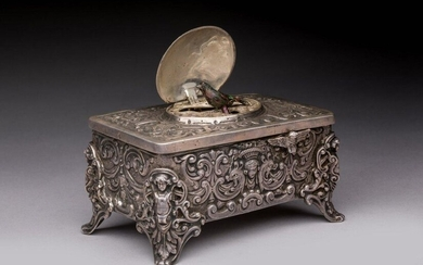 AUTOMATIC MUSIC BOX with BIRD BIRD in silver. On the lid, a medallion engraved in relief of a head carrying a flowery basket, in a frame of bird couples at the fountain, opens to discover an automaton bird adorned with natural feathers. The front...