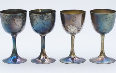 FOUR JAPANESE SILVER WINE CUPS Two with a pine tree design, one with a bird and grasses design, and one with a lake and mountain des...