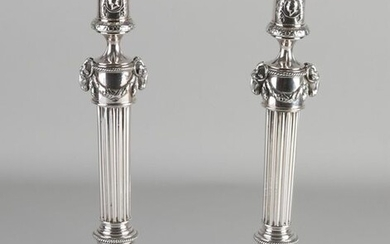 Set of capital silver candlesticks, Empire style, on a square base with flower border and garlands. Equipped with a pillar with medallions with portraits, wreaths, a piece of column and above that a piece decorated with garlands and ram's heads. The...