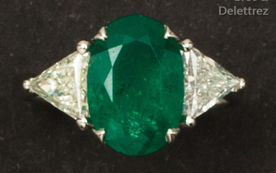White gold ring set with an oval emerald...