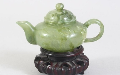 A CHINESE MOTTLED GREEN JADE TEA POT ON PIERCED AND