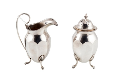 A GEORGE V SILVER CREAM JUG AND SUGAR SIFTER of faceted form...