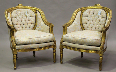 A pair of 20th century Louis XVI style giltwood showframe tub back armchairs, upholstered in foliate