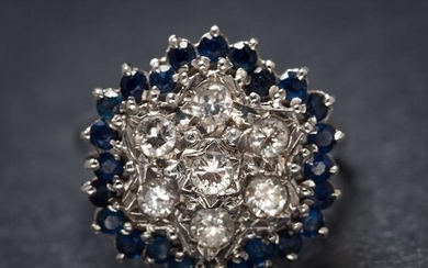 A sapphire and diamond circular cluster ring: set with round...