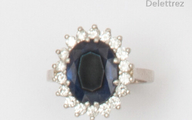 """Flower"""" ring in white gold, adorned with an oval sapphire in a setting of brilliant-cut diamonds. Finger size: 50. P. Rough: 6.6g."""