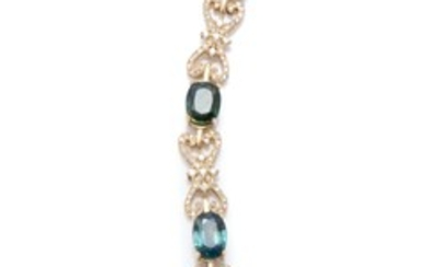 A 18CT GOLD SAPPHIRE AND DIAMOND BRACELET; featuring 7 blue/green oval cut sapphire set links totalling approx. 7.00cts, between 6 f...