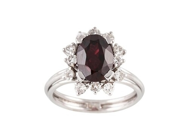 A GARNET AND DIAMOND CLUSTER RING, the oval garnet to a bril...