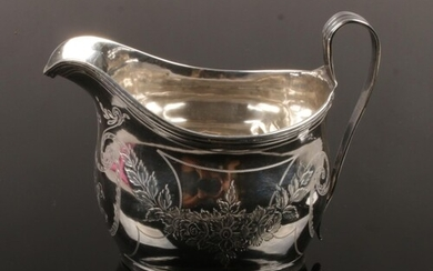 A George III silver cream jug. With reeded strap handle and ...