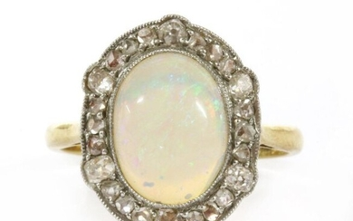 A gold opal and diamond ring, an oval cabochon opal, approximately milligrain set to a halo surround of old brilliant and rose cut diamonds, grain set to a milligrain edge. The white faced setting plate to a yellow gold chenier gallery, tapered chenier...